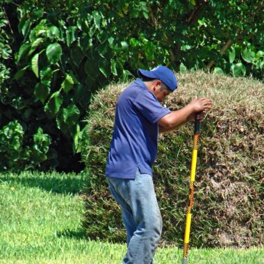 man using a manual post hole digger