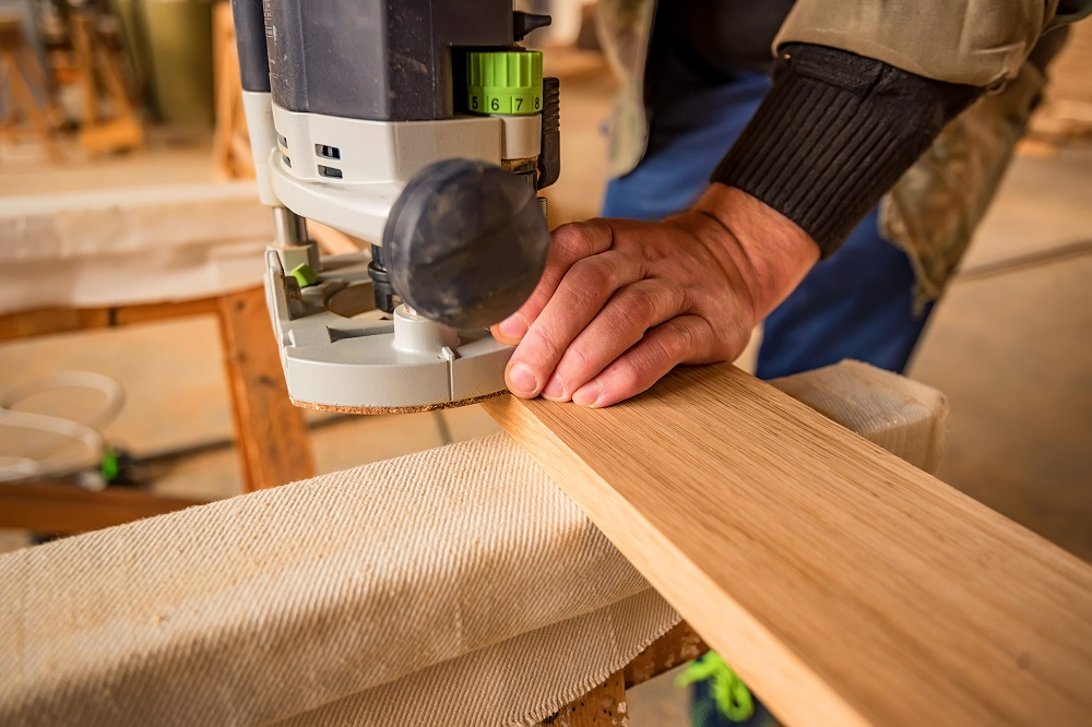 man processing wood using a router