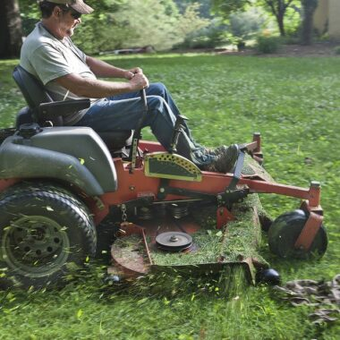 landscaper using a riding lawnmower